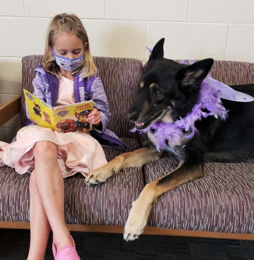 Girl reading to a therapy dog on a couch